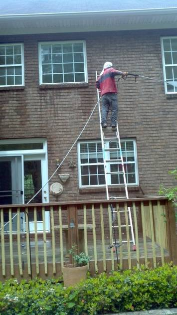 Zelaya Jr. technician on a ladder pressure washing the side of a two story home.